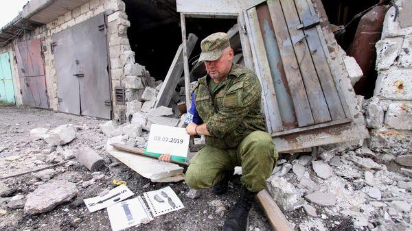 Офицер Совместного центра контроля и координации фиксирует повреждения гаражей в результате артобстрела Горловки.