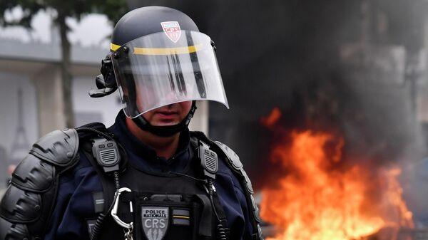 Полицейский во время протеста после парада в День взятия Бастилии в Париже, Франция. 14 июля 2019