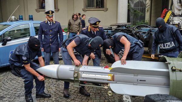 Итальянские полицейские переносят ракету класса воздух-воздух после обнаружения тайника с оружием и боеприпасами в Турине