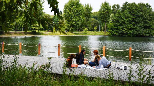 Посетители парка отдыхают на берегу водоема в парке Терлецкая дубрава в Москве