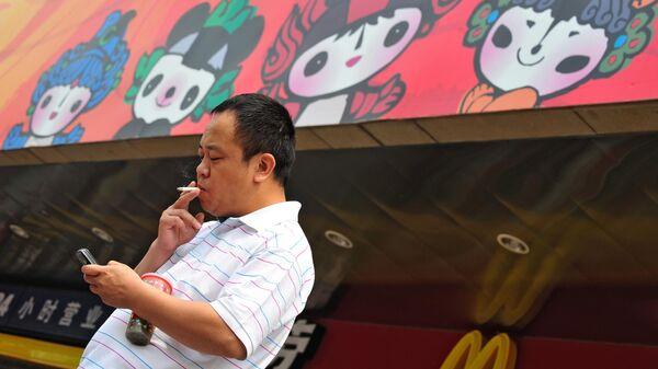 Мужчина курит на Олимпийских играх в Пекине
