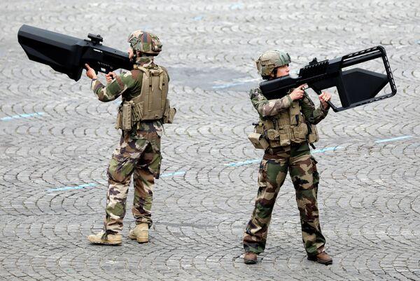 Солдаты французской армии с противотанковыми пушками во время традиционного военного парада в День взятия Бастилии на Елисейских Полях в Париже