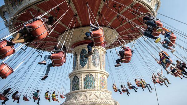 Посетители одного из парков развлечений катаются на карусели