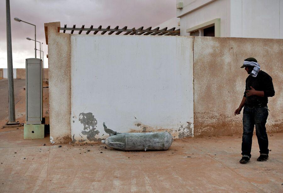 Житель города Рас-эль-Ануфа стоит рядом с неразорвавшейся авиабомбой
