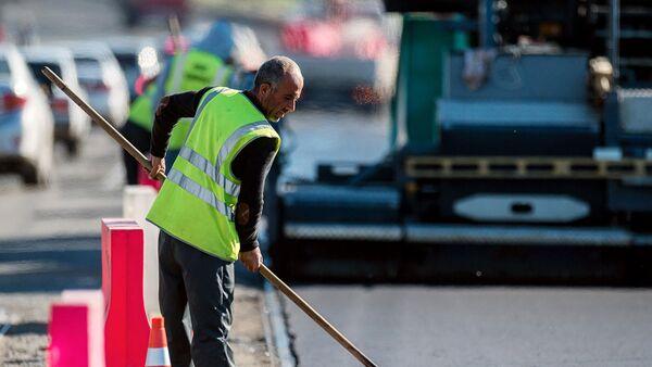 Рабочий во время ремонта дорожного покрытия
