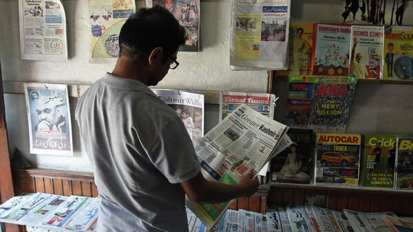 Мужчина читает газету в киоске в Сринагаре