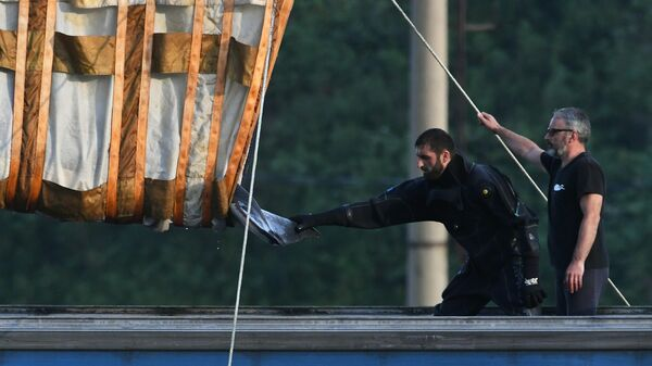 Специалисты перегружают косатку из китовой тюрьмы на машину, с помощью которой ее отправят к Охотскому морю для выпуска