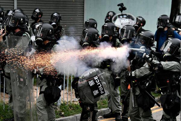 Сотрудники полиции разгоняют демонстрантов слезоточивым газом в районе Юньлон в Гонконге
