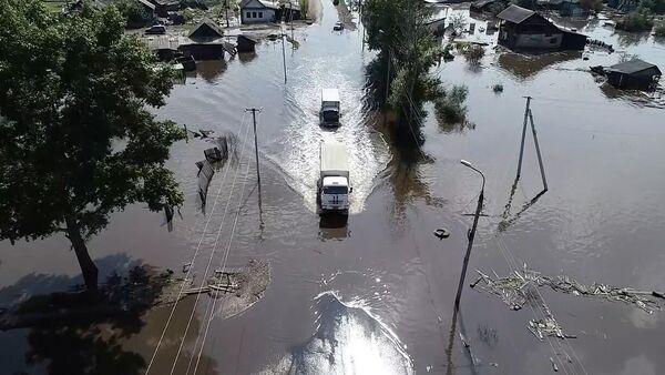 Машины МЧС РФ едут по затопленным улицам в одном из районов Иркутской области
