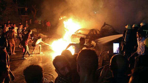 Люди пытаются загасить огонь после взрыва возле Национального института рака, Каир, Египет. 4 августа 2019