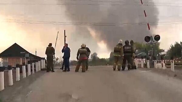 Сотрудники пожарной службы в районе воинской части под Ачинском, где произошли пожар и взрывы на складе хранения артиллерийских боеприпасов. Стоп-кадр с видео