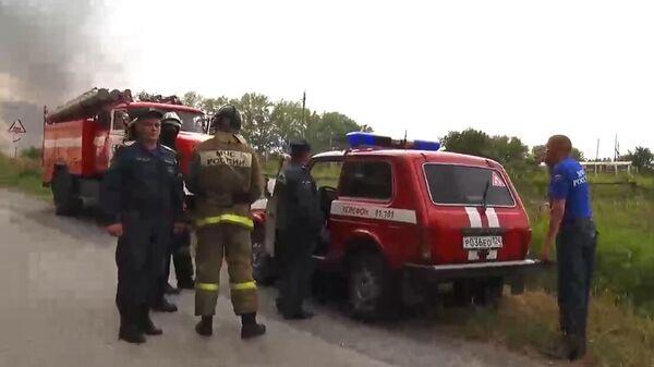 Сотрудники МЧС в районе воинской части под Ачинском, где произошли пожар и взрывы на складе хранения артиллерийских боеприпасов. Стоп-кадр с видео