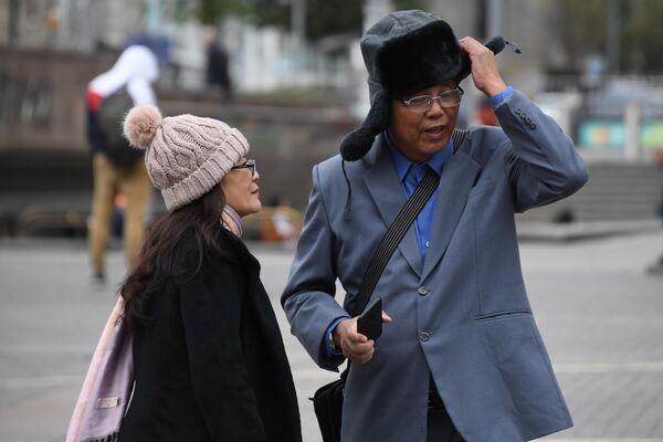 Иностранные туристы одевают теплые головные уборы на Манежной площади