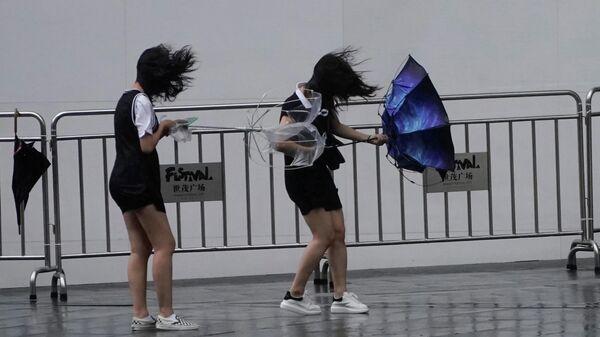 Девушки во время прохождения супертайфуна Лекима в Шанхае, КНР. 10 августа 2019