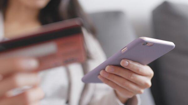 Девушка со смартфоном и банковской картой