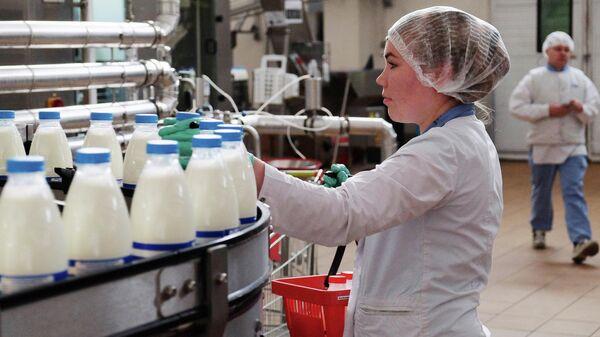 Сотрудница на производственной линии по упаковке молока