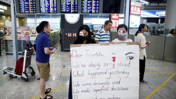 Участники акции протеста в аэропорту Гонконга с плакатом с извинениями перед туристами