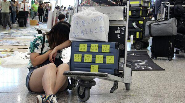 Пассажиры в международном аэропорту Гонконга во время акции протеста