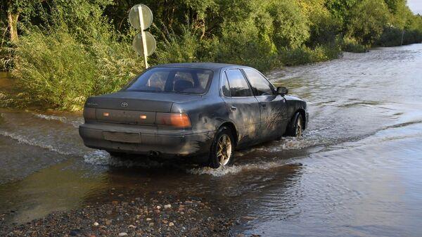 Автомобиль на подтопленной паводком дороге в районе Уссурийска
