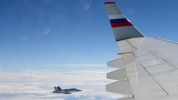 Истребитель Ф/A-18 Хорнет ВВС Швейцарии сопровождает российский пассажирский самолет. 19 августа 2019