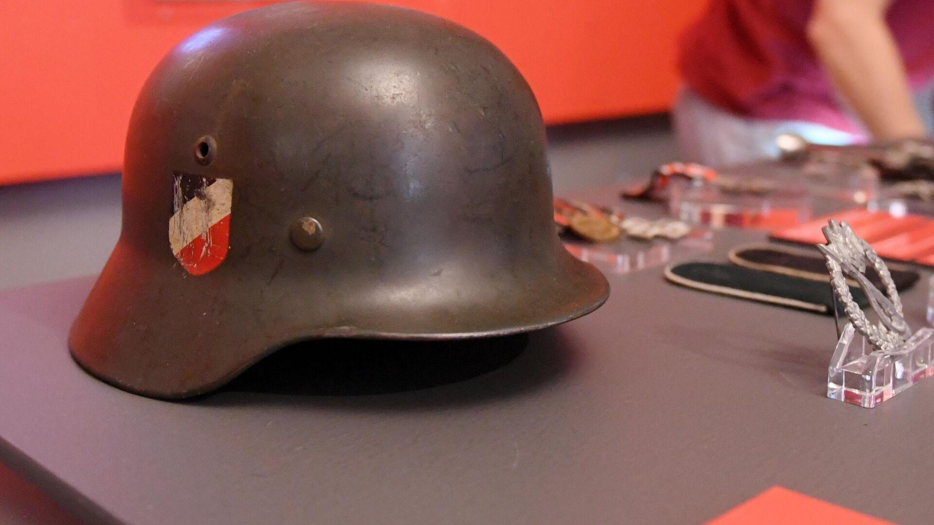 Стальной шлем М-35 образца 1935 года (Германия, 1-я половина XX века), представленный на открытии историко-документальной выставки 1939 год. Начало Второй мировой войны в Выставочном зале федеральных архивов в Москве - РИА Новости, 1920, 14.10.2020