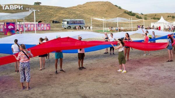 Флешмоб с развёртыванием 30-метрового флага Российской Федерации в честь Дня Российского Флага на территории фестиваля творческих сообществ Таврида-АРТ в бухте Капсель в Судаке