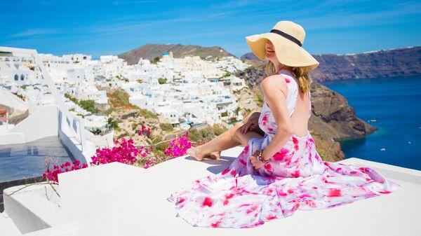 Девушка фотографируется  в городе Ия на Санторини, Греция