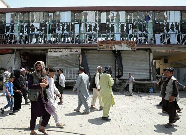 Люди проходят мимо здания с выбитыми окнами на месте взрыва в Кабуле, Афганистан. 7 августа 2019