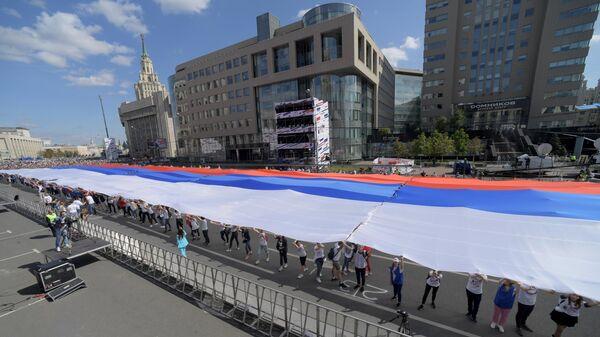 Участники флешмоба в честь Дня государственного флага России на проспекте Сахарова в Москве