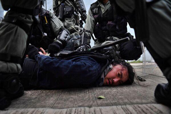 Сотрудники полиции задерживают протестующего в Коулуне, Гонконг