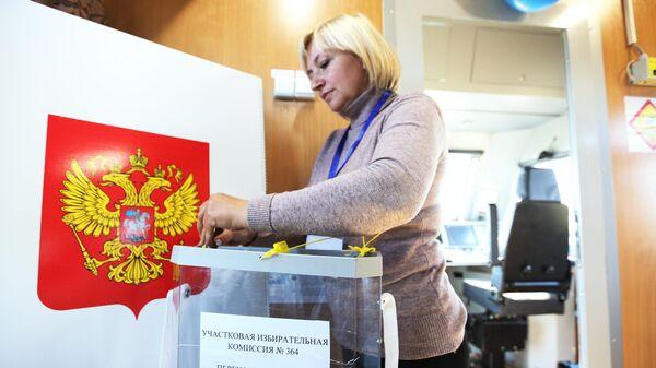 Член участковой избирательной комиссии пломбирует избирательную урну после досрочного голосования на выборах губернатора Мурманской области