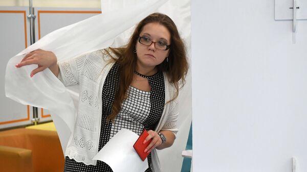 Жительница Москвы голосует на выборах в Московскую городскую Думу на избирательном участке № 90