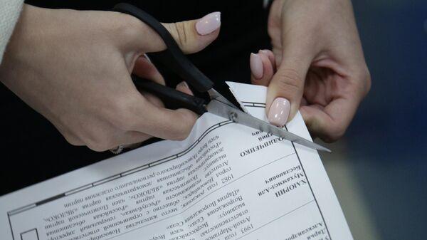 Члены избирательной комиссии проводят процедуру гашения неиспользованных бюллетеней на избирательном участке