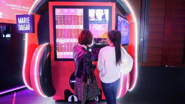 Девушки выбирают товары на выставке T-Mall в Шанхае, Китай