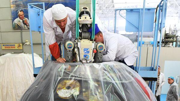 Сотрудники ракетно-космической корпорации Энергия извлекают робота Федора из спускаемого аппарата космического корабля Союз МС-14 после полета на МКС