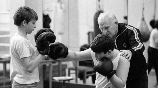 Старший тренер по боксу Комитета по физической культуре и спорту при Совете Министров СССР, заслуженный тренер СССР Виктор Огуренков (справа) проводит тренировку со своими воспитанниками.