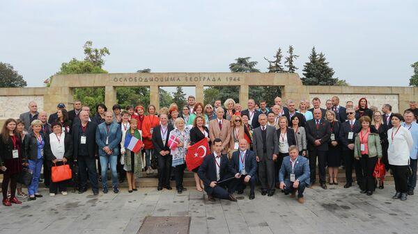 Участники международной конференции Память победителей фотографируются около Мемориала освободителям Белграда