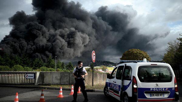 Полицейский на шоссе Ле-Пети-Кевилле, перекрытом в связи с задымлением из-за пожара на заводе  Lubrizol в Руане, Франция. 26 сентября 2019