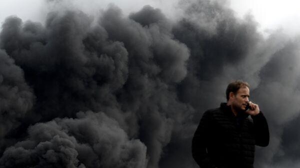 Мужчина на дороге в Ле-Пети-Кевилли в дыму от пожара на фабрике Lubrizol. 26 сентября 2019