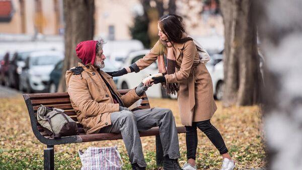 Девушка помогает бездомному мужчине
