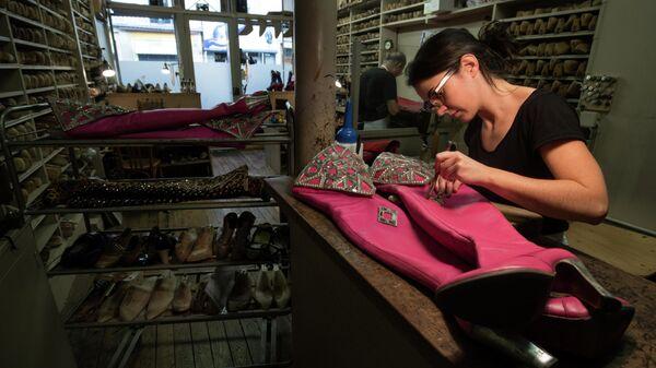Сапожник работает в Мулен Руж в Париже, Франция