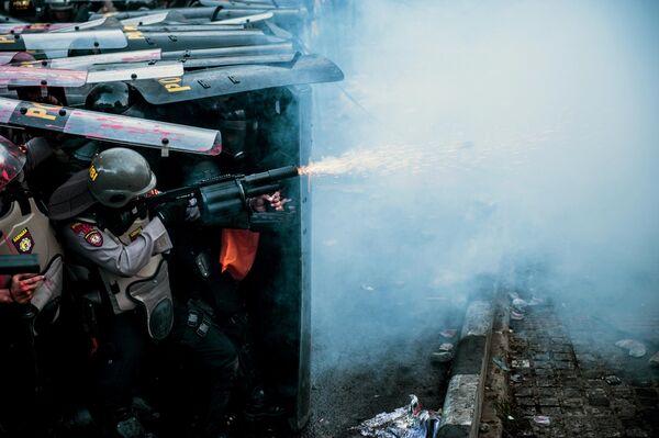 Полиция применяет слезоточивый газ во время акции протеста студентов в Бандунге, Индонезия