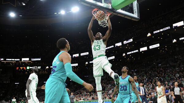 Игрок БК Бостон Селтикс Джавонте Грин забрасывает мяч в корзину в предсезонном матче Национальной баскетбольной ассоциации против БК Шарлотт Хорнетс