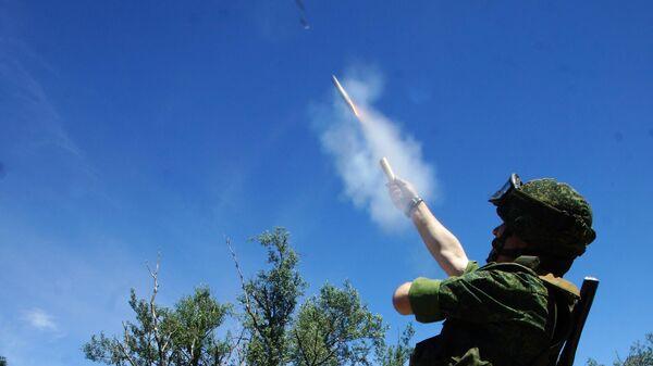 Военнослужащий ЛНР запускает сигнальную ракету белого цвета