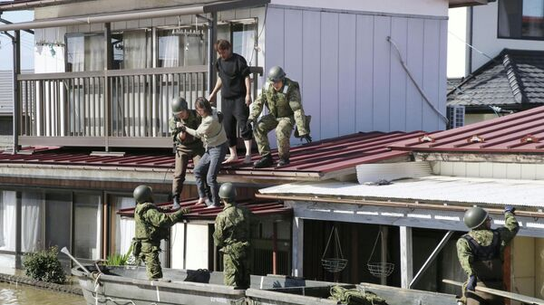 Солдаты Сил самообороны Японии эвакуируют местных жителей во время прохождения тайфуна Хагибис. 13 октября 2019