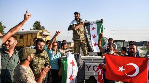 Бойцы поддерживаемой Турцией сирийской вооруженной оппозиции празднуют взятие города Телль-Абъяд.