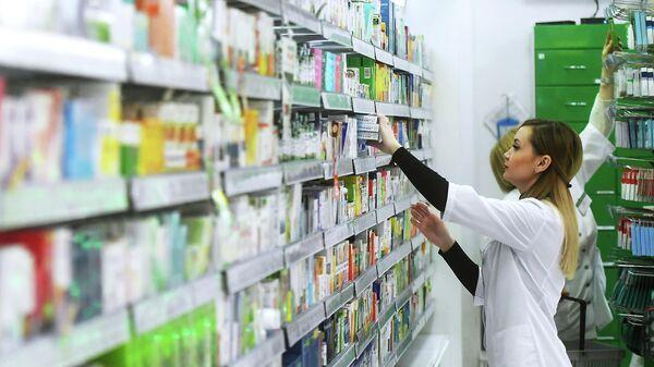 Фармацевт раскладывает лекарственные препараты в аптеке