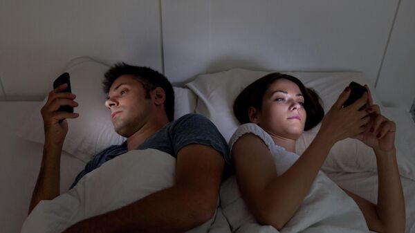Молодая пара в кровати со смартфонами