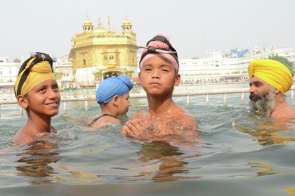 Люди празднуют годовщину рождения четвертого сикхского Гуру Рам Даса в Золотом храме