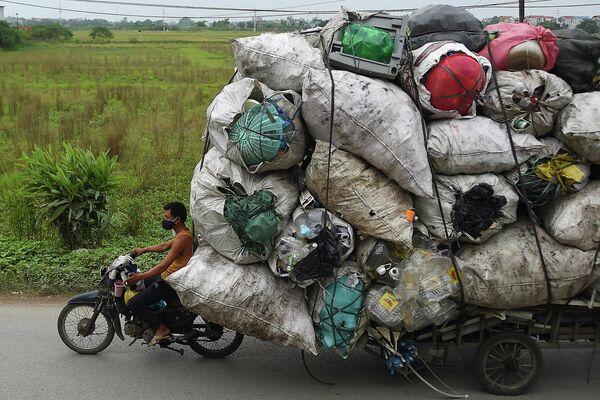 Сборщик мусора везет пластик на переработку в пригороде Ханоя